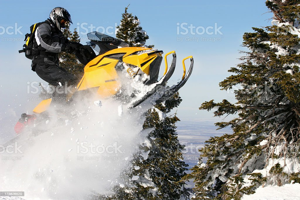 A person landing a jump on a snowmobile stock photo