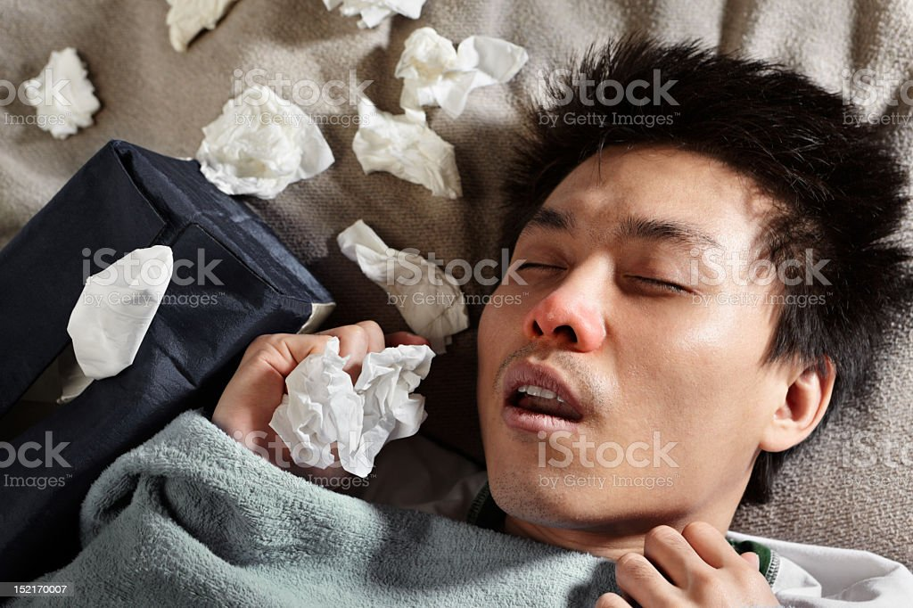 A person laying in bed who is sick  stock photo