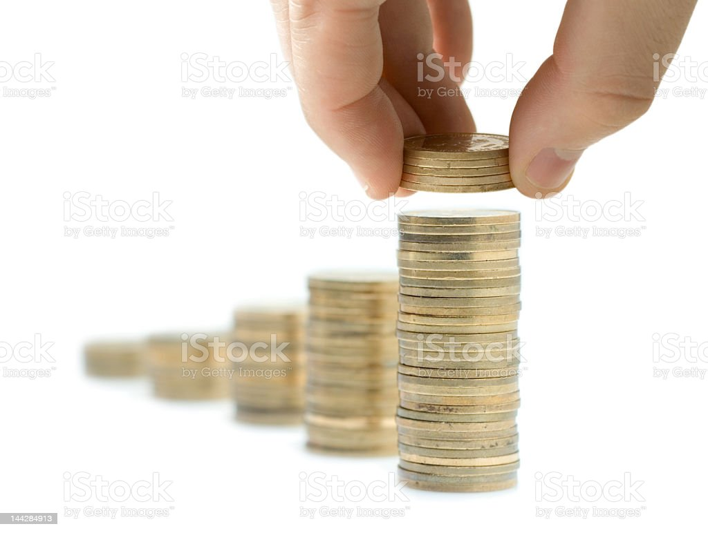 Person laying more quarters on top of a pile of quarters stock photo