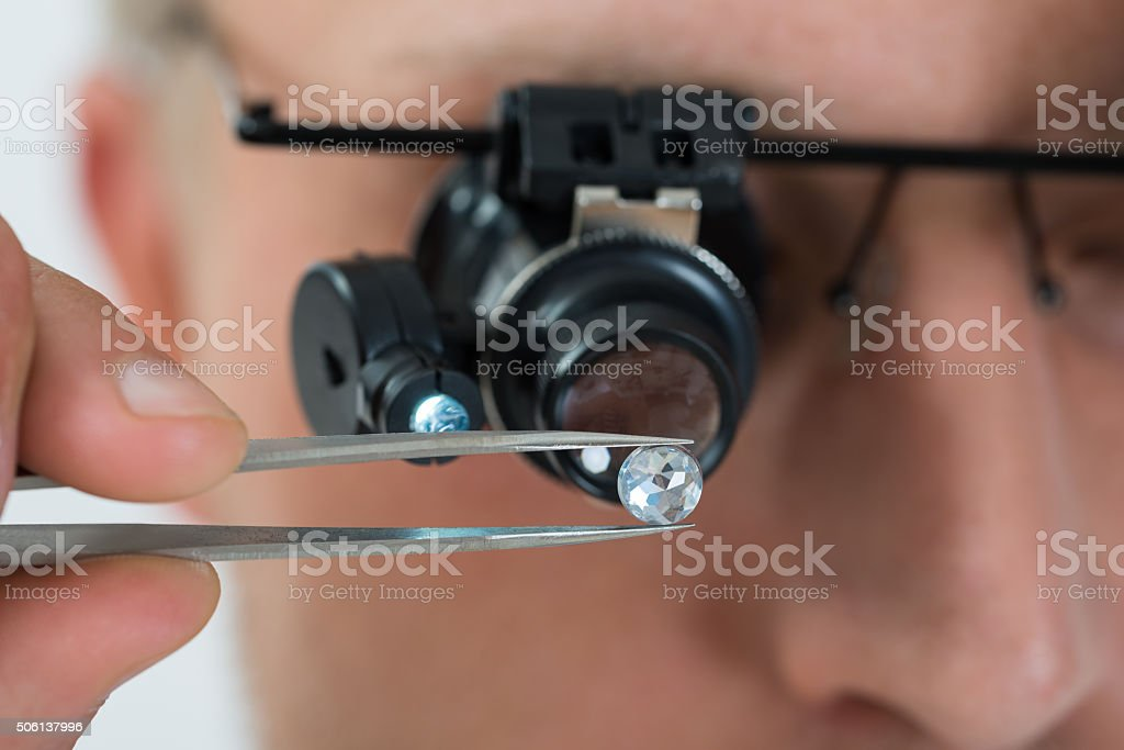 Person Looking At Diamond With Magnifying Loupe stock photo
