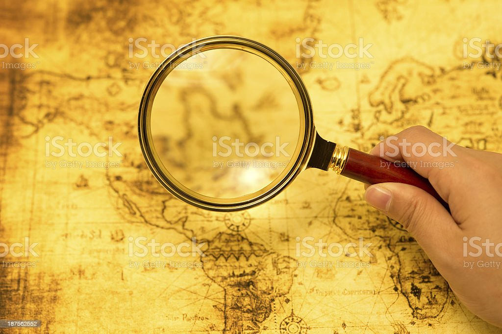 Person Looking at Map with Magnifying Glass royalty-free stock photo