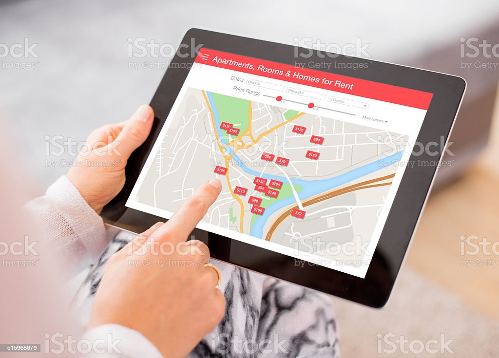 Person looking for places to stay on digital tablet app stock photo