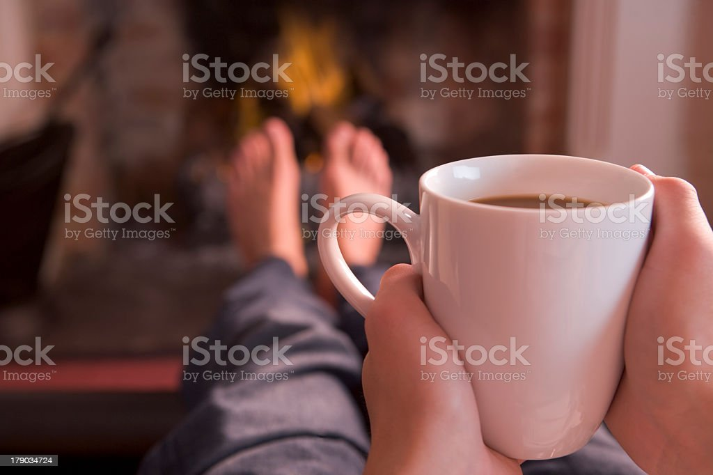 Person lying down holding a white cup of coffee stock photo