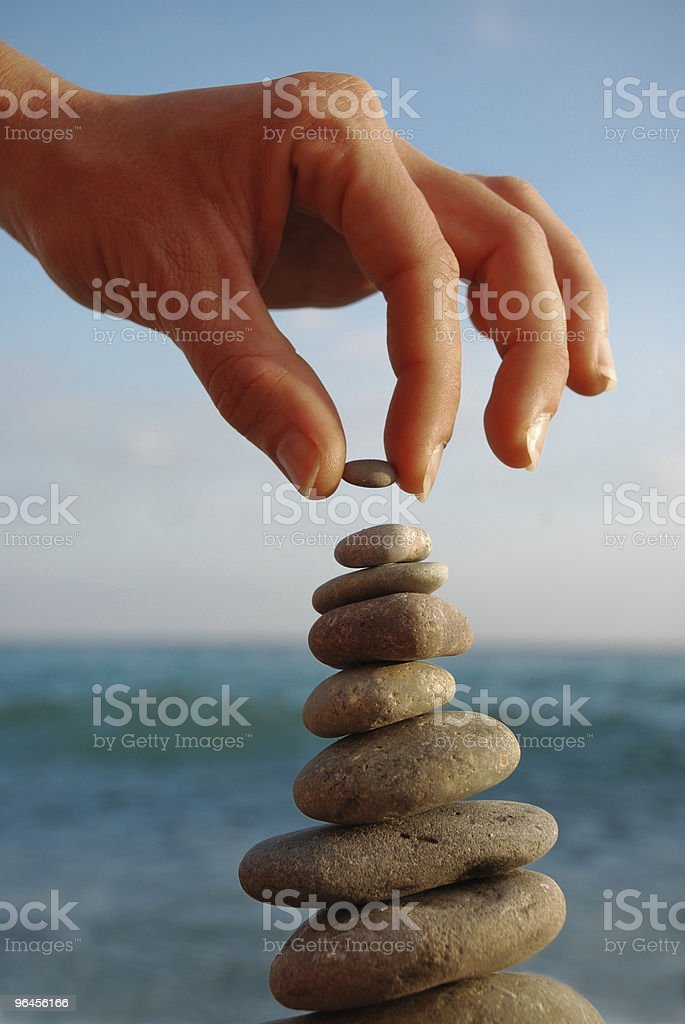 Person making a tower made of stones at the beach stock photo