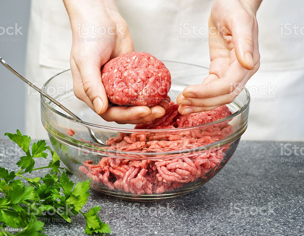 A person making meatballs with ground beef stock photo