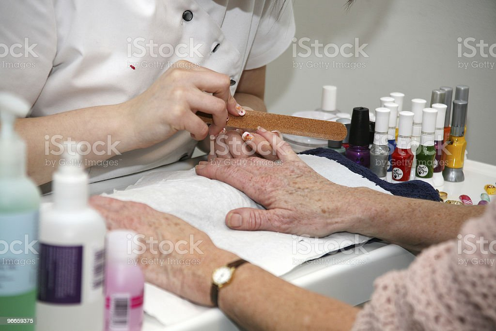 Person manicuring elderly woman's nails royalty-free stock photo