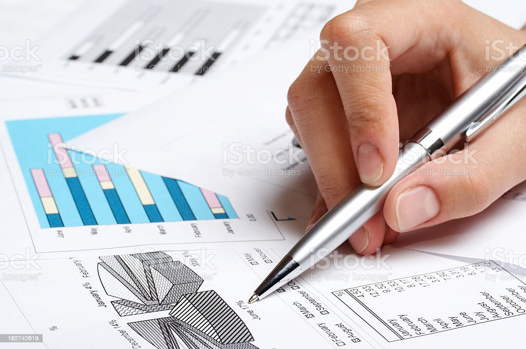 A person marking a pie chart on paper royalty-free stock photo