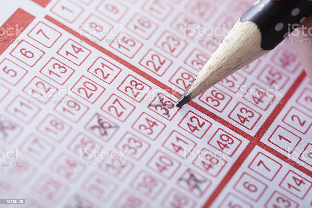 Person Marking Number On Lottery Ticket stock photo