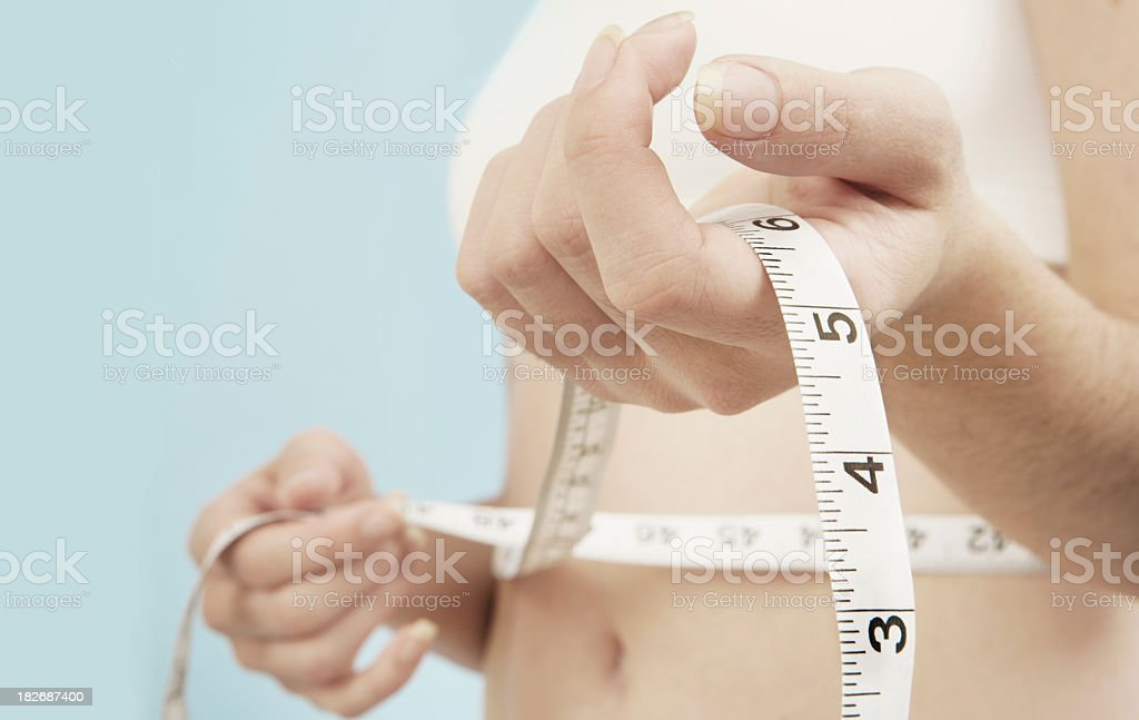 Person measuring their bare waist with a white tape measure royalty-free stock photo