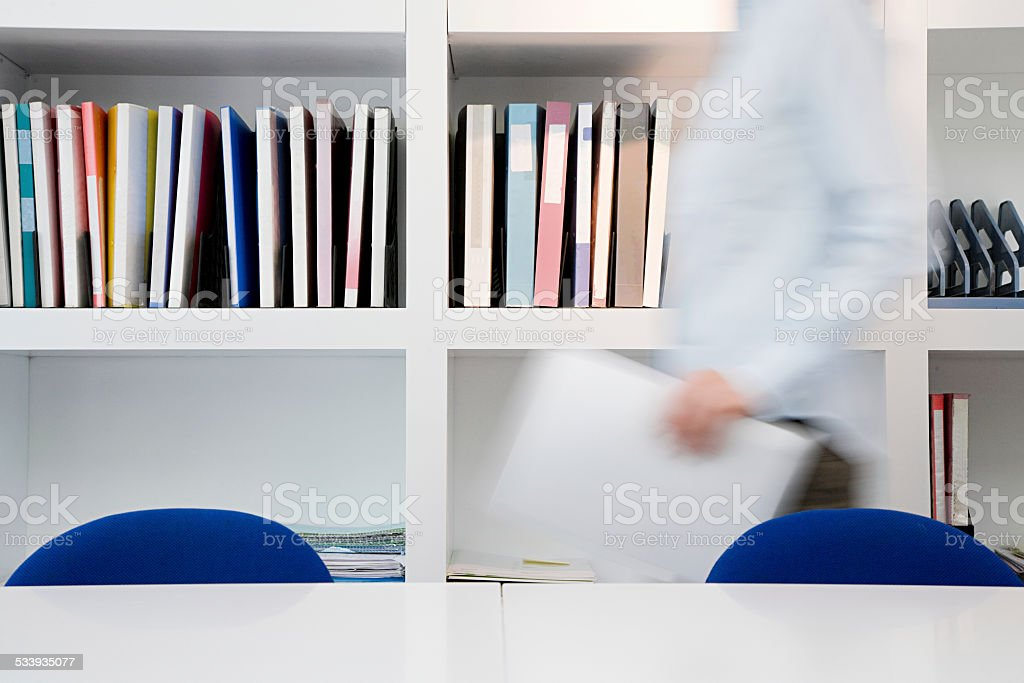 Person moving through office stock photo