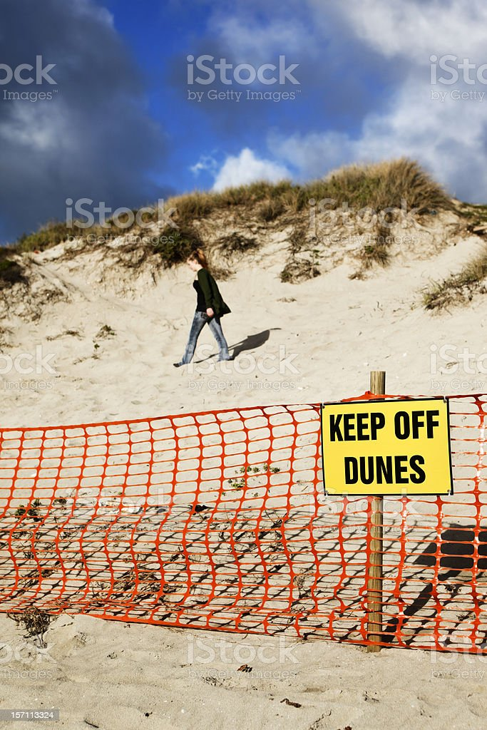 Person not obeying Keep Off Dune sign stock photo