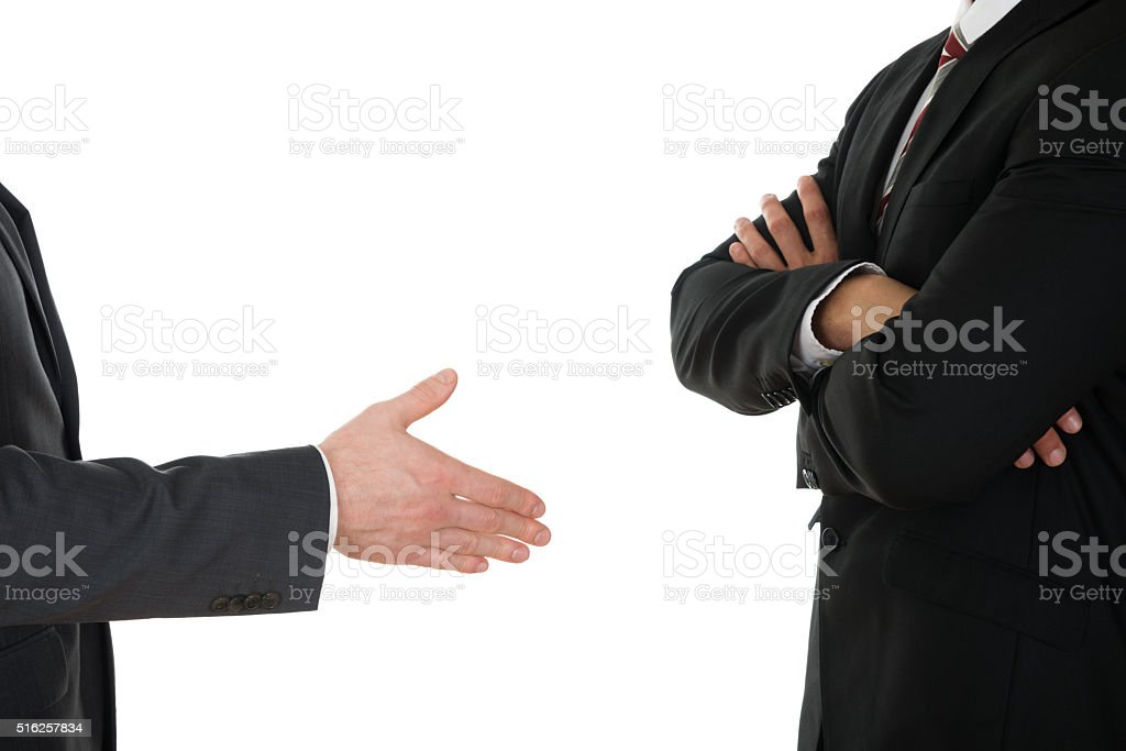 Person Offering Handshake To Businessman With Arm Crossed stock photo