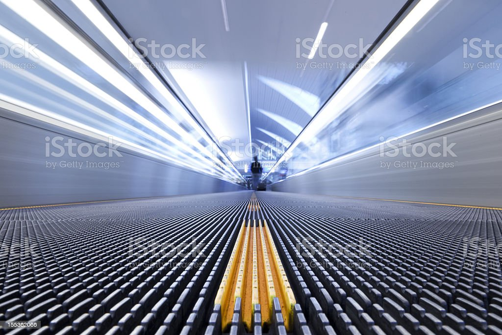 Person on a moving escalator with yellow stripes stock photo