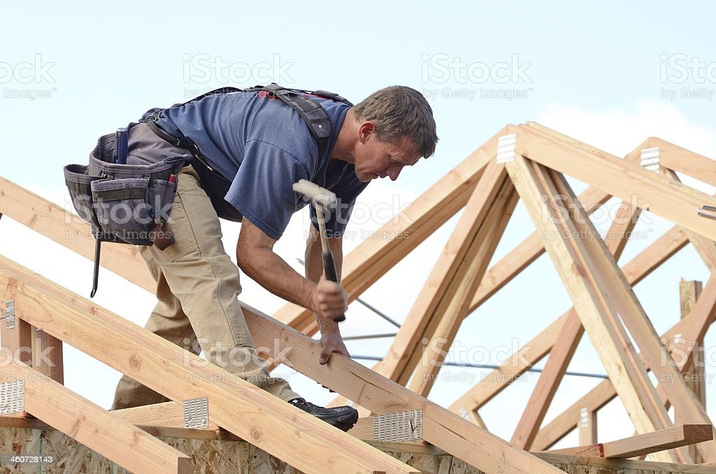 A person on a roof rafter using a hammer stock photo