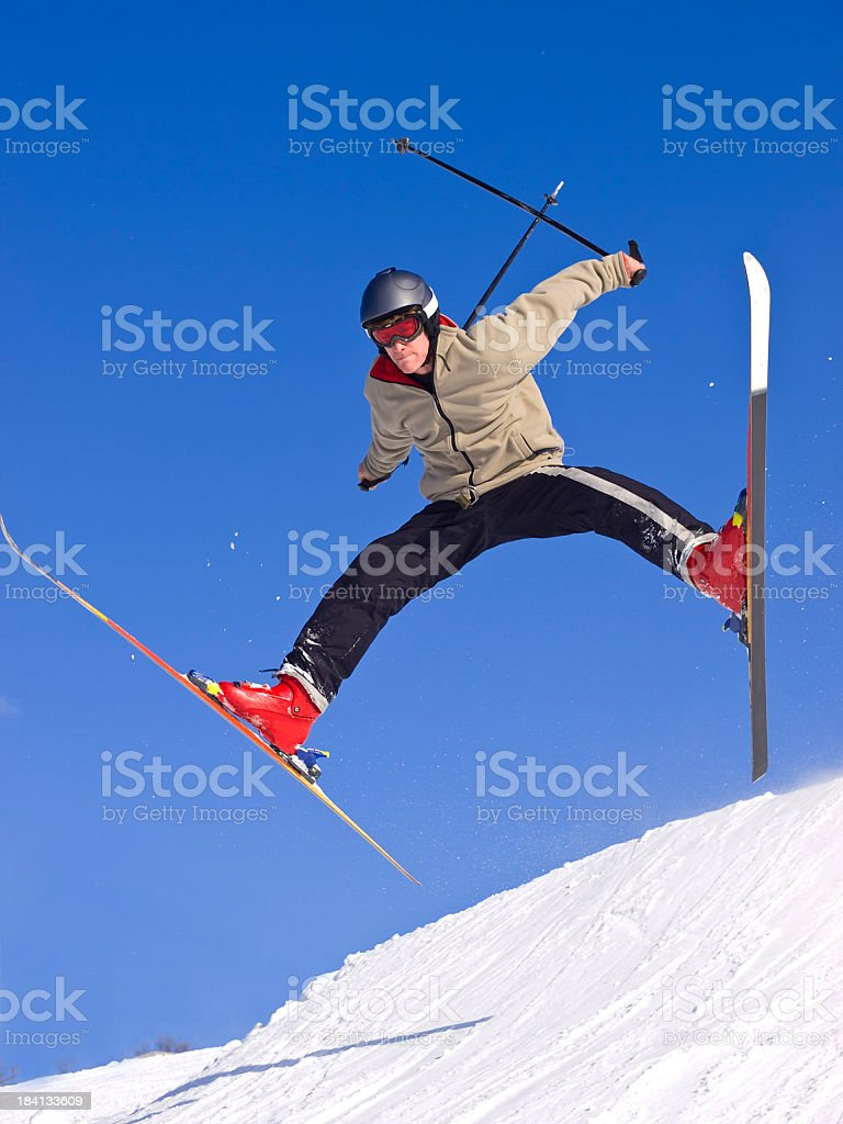 Person on skis jumping down a snowy hill stock photo