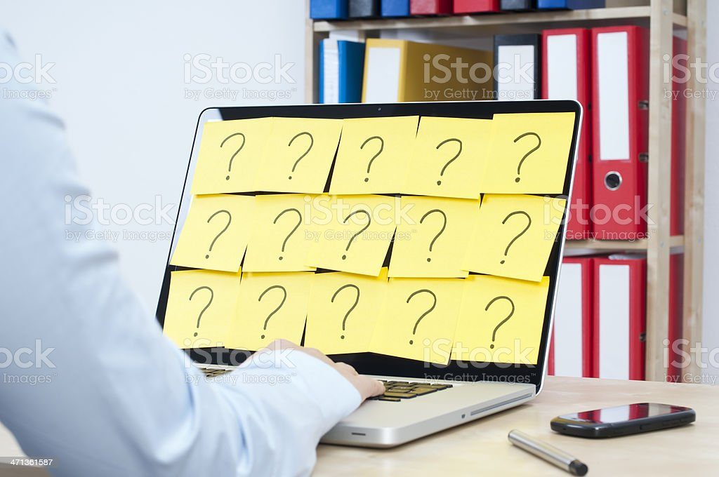 Person on their laptop covered in question marks stock photo
