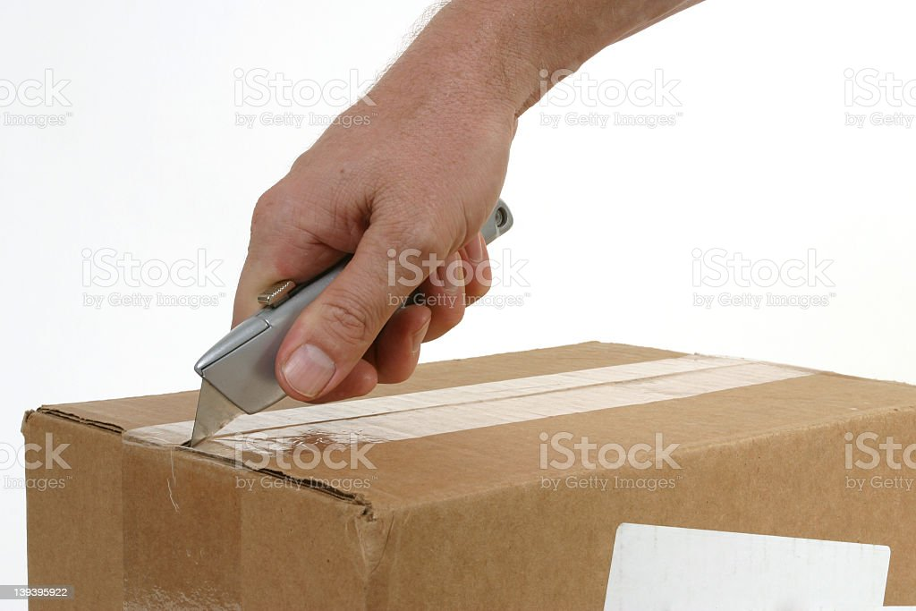 Person opening a cardboard box with a box cutter stock photo