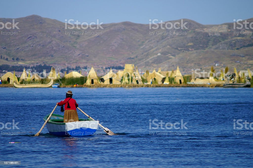 Person paddling on a small boat at Uros Islands stock photo