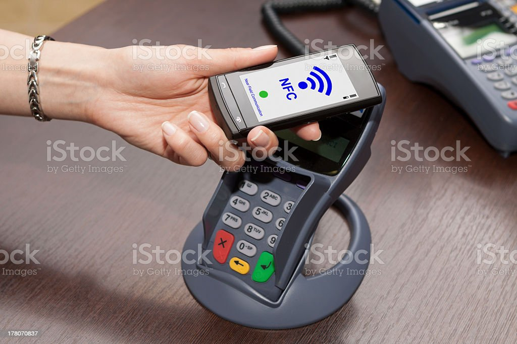 Person paying for their goods using near field communication stock photo