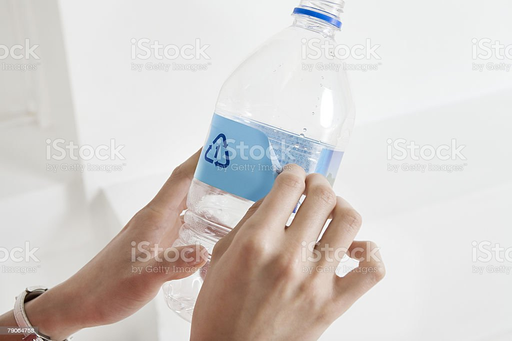A person peeling off a label off a bottle royalty-free stock photo