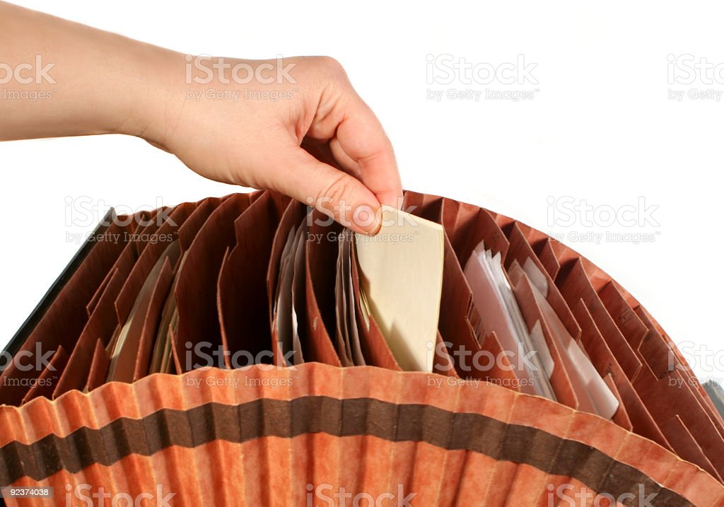 A person picking a file folder out of an accordion folder royalty-free stock photo