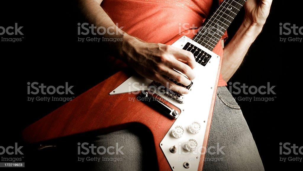 A person playing a rock and roll guitar stock photo