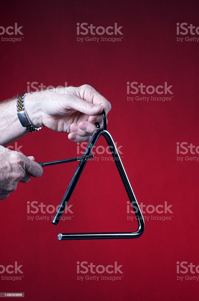 A person playing a triangle on a red background royalty-free stock photo
