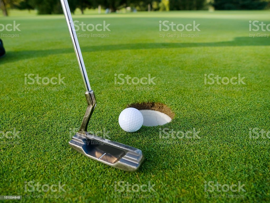 A person playing golf hitting the ball in the hole stock photo