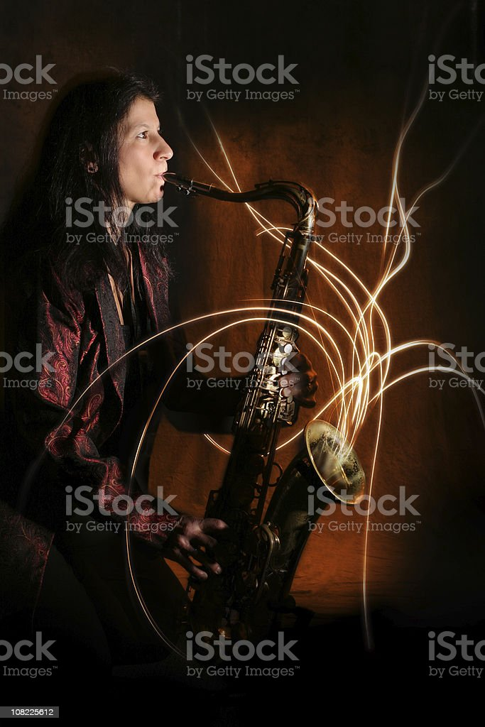 Person Playing Saxophone with Light Streaming From Instrument stock photo
