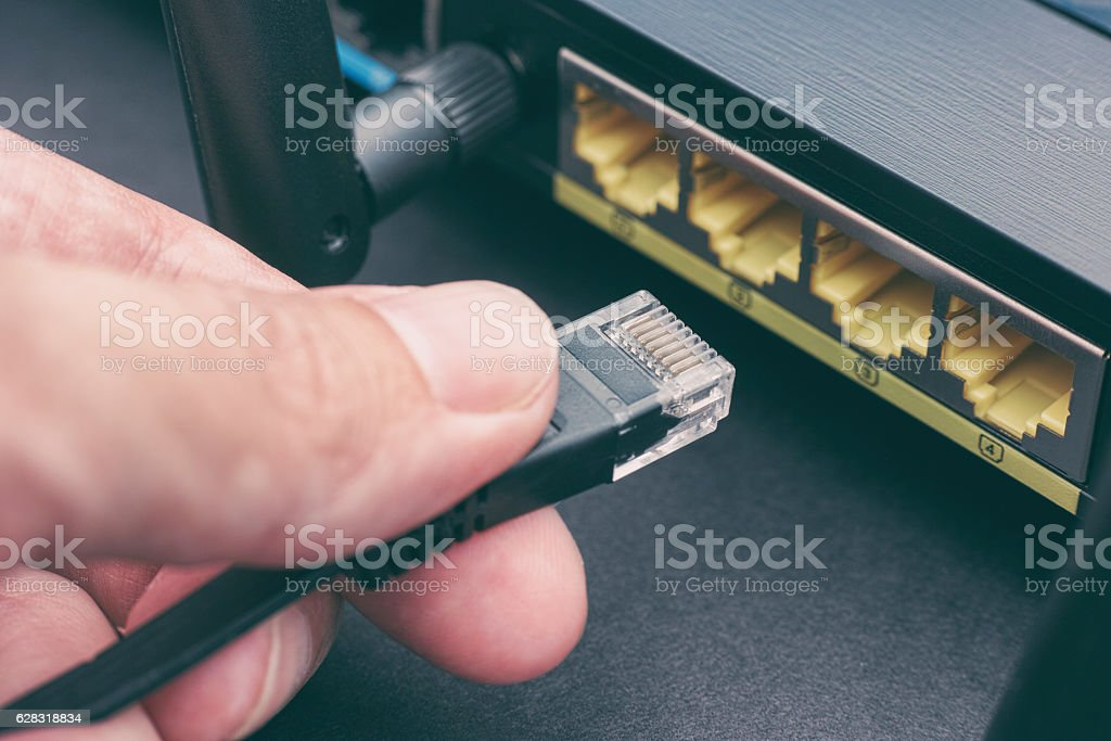 Person plugging in cable to wireless router stock photo