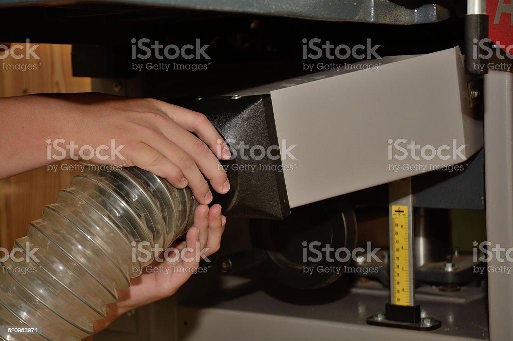 Person steckt Absaugschlauch an Hobelmaschine stock photo