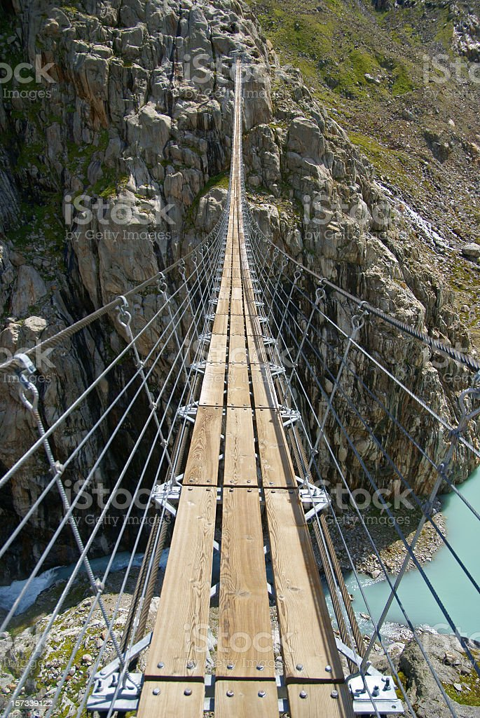 Person point-of-view of a rope bridge over empty space stock photo