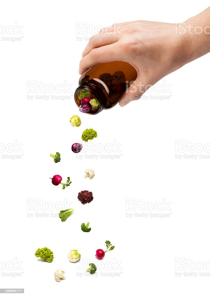 A person pouring out a pill jar with tiny vegetables royalty-free stock photo