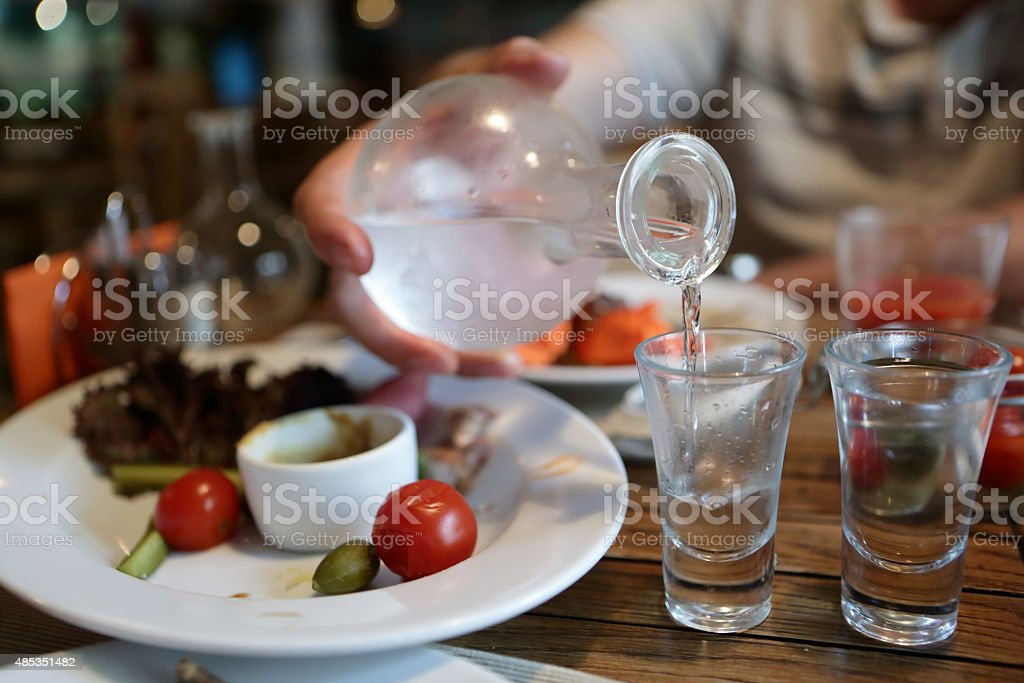 Person pouring vodka from the decanter stock photo