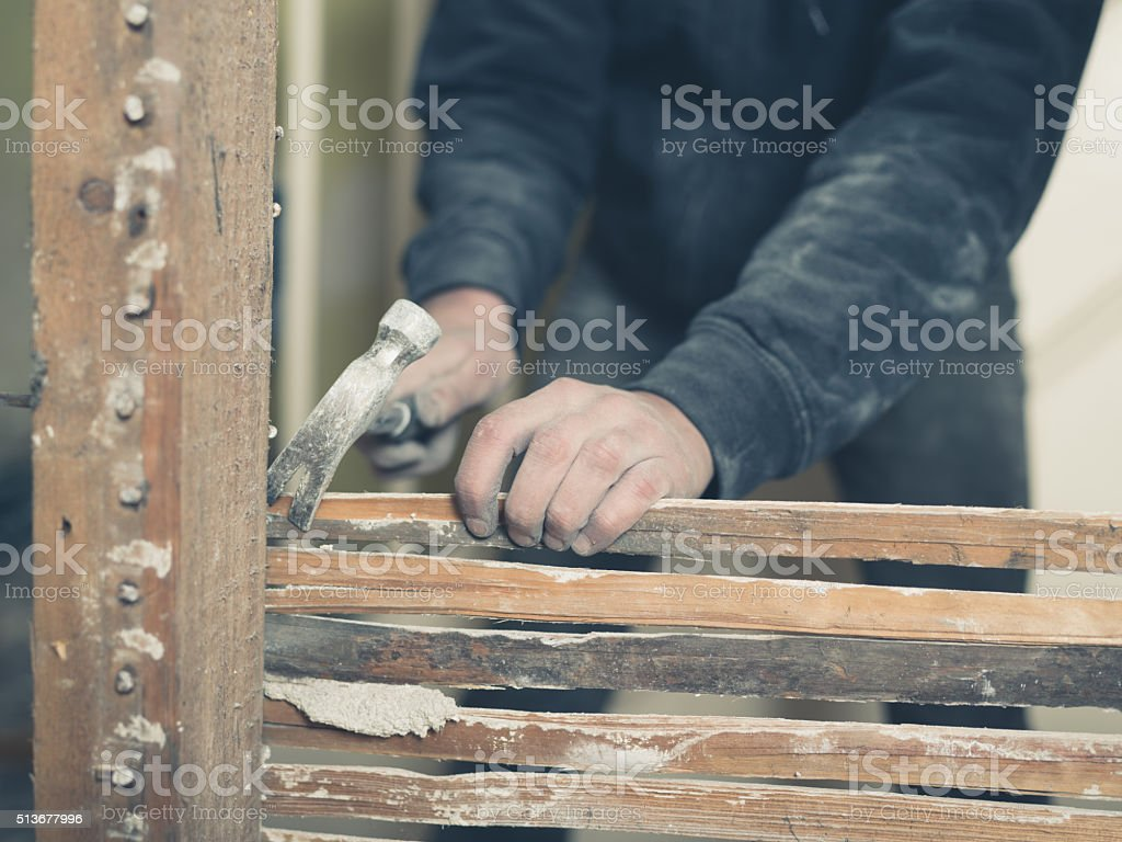 Person pulling out nails of wattle stock photo
