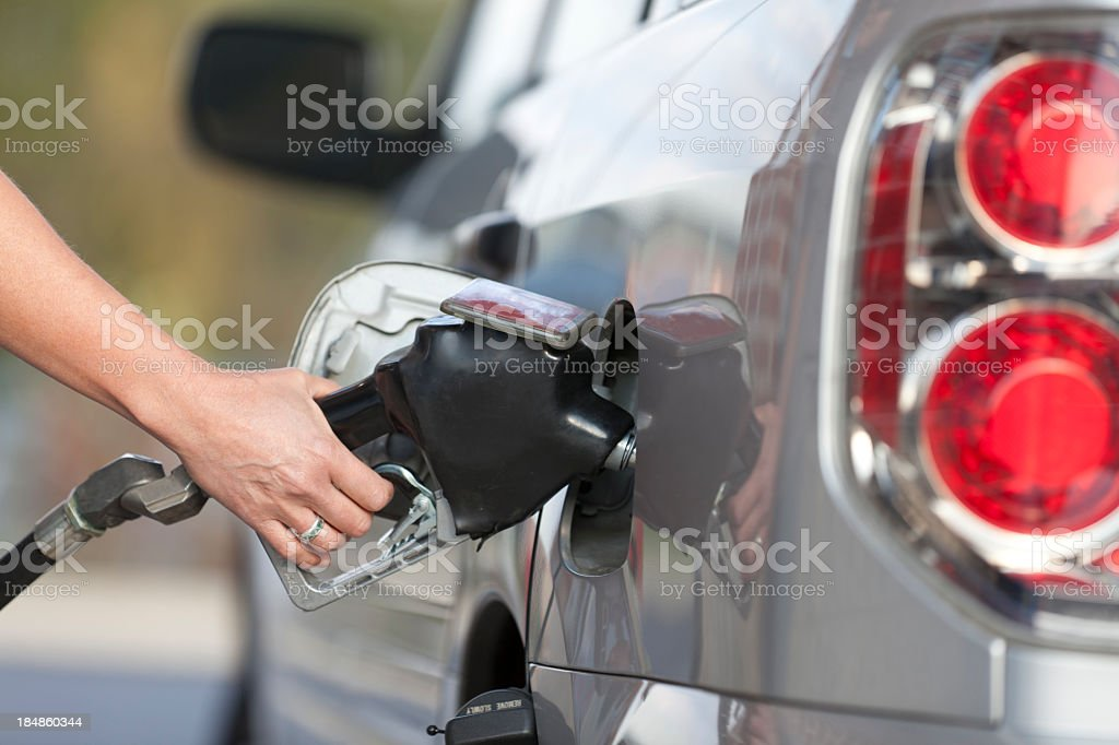 A person pumping gas into their grey vehicle  stock photo