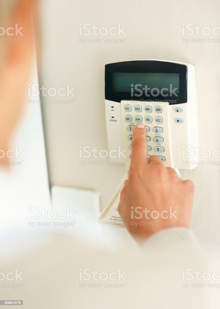 Person putting in pin code to home alarm system royalty-free stock photo