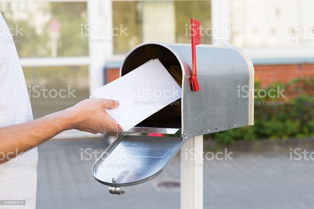Person Putting Letters In Mailbox stock photo