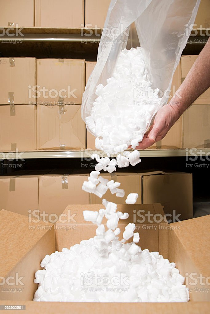 Person putting packing peanuts in box stock photo