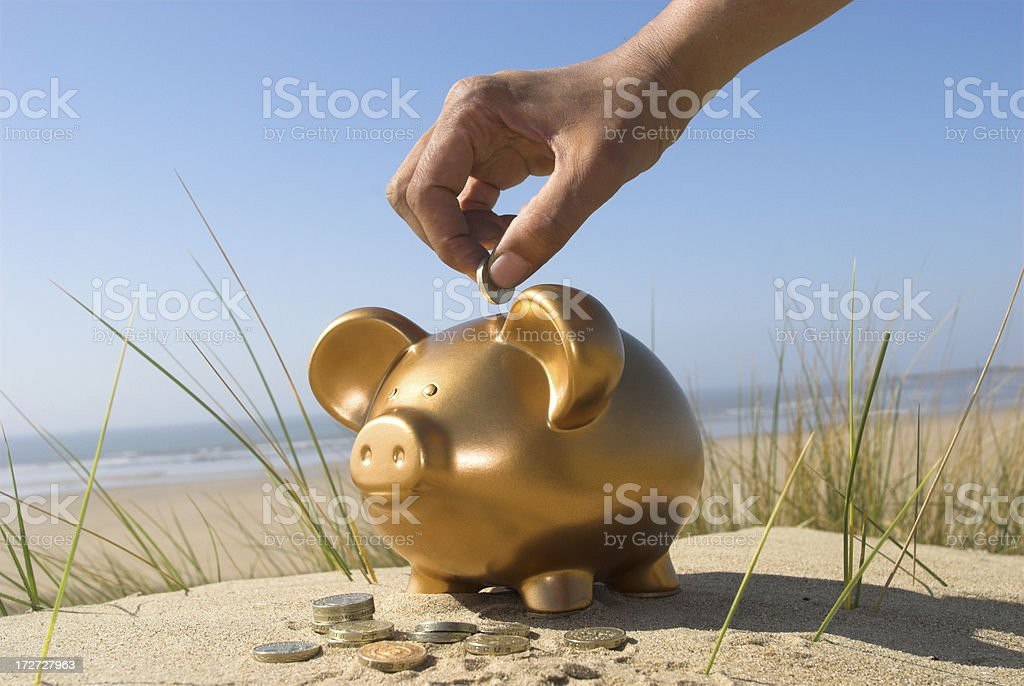 Person putting vacation savings into a golden piggy bank royalty-free stock photo
