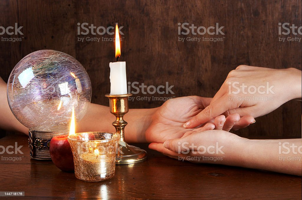 Person reading a palm on a table with a crystal ball stock photo