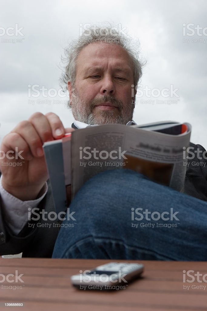 Person reading magazine, with cell phone close by  royalty-free stock photo