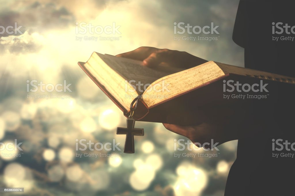 Person reads bible with rosary stock photo