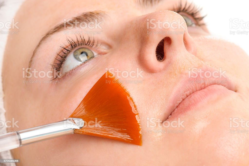 A person receiving a facial with a brush on their cheek stock photo