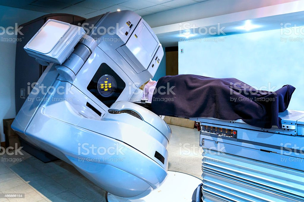Person receiving radiation therapy for cancer treatment in linear acelerator stock photo
