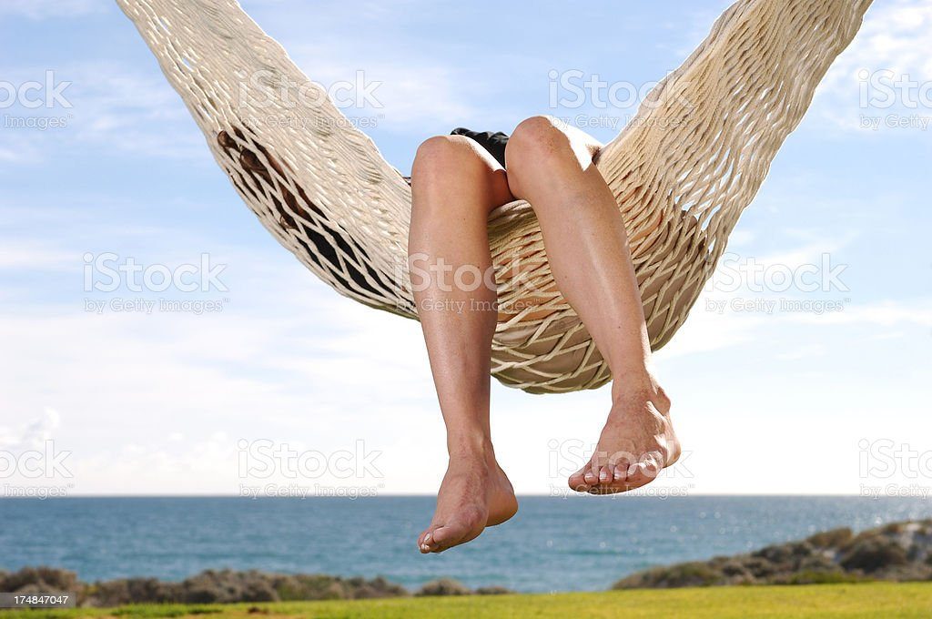 Person relaxing in a swinging hammock at the beach. royalty-free stock photo