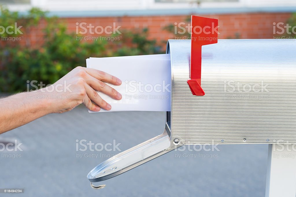 Person Removing Letters From Mailbox stock photo