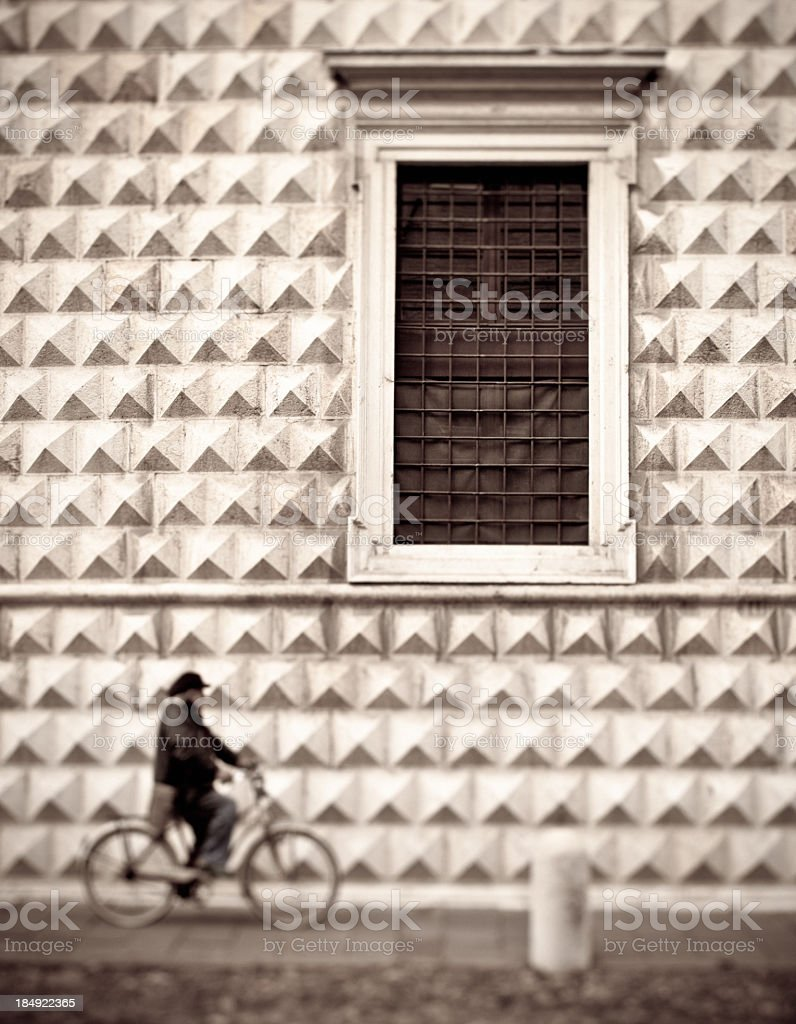 Person Riding Bicycle on Italian Street, Sepia Toned stock photo