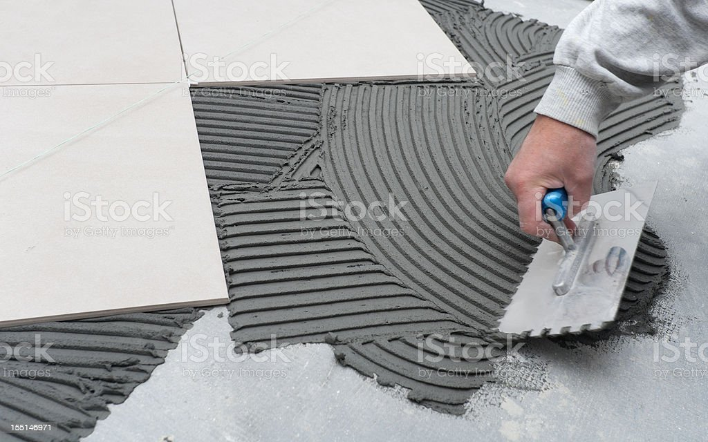 Person scrapes concrete at a construction site royalty-free stock photo