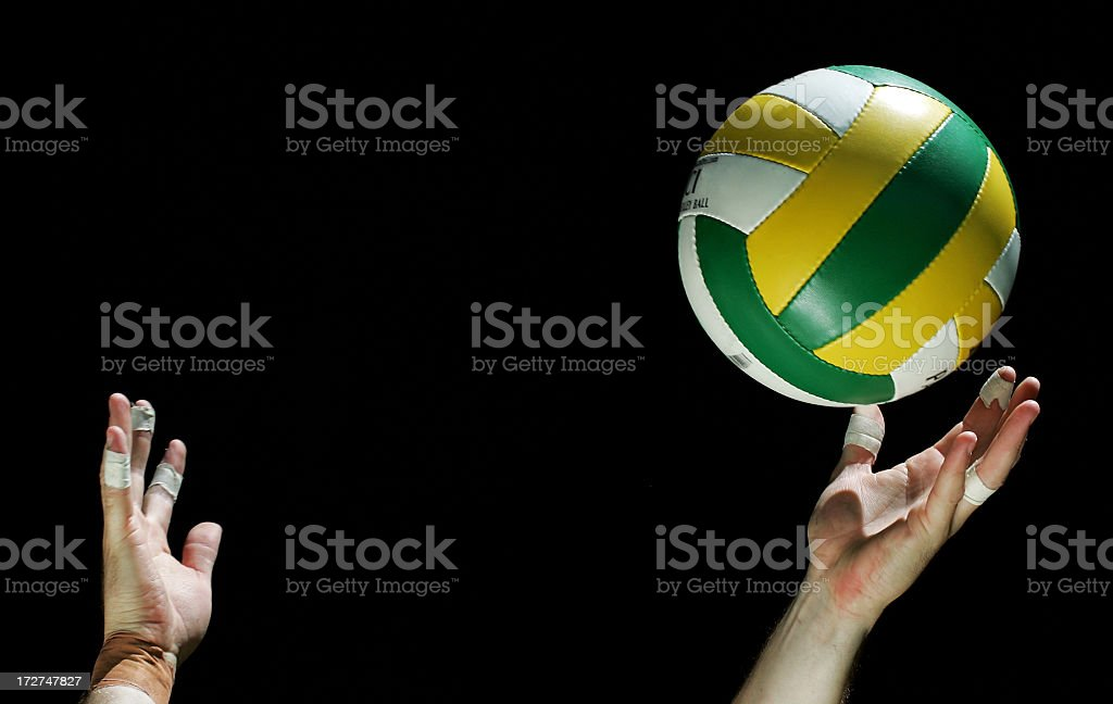 Person serving a volleyball on a black background royalty-free stock photo